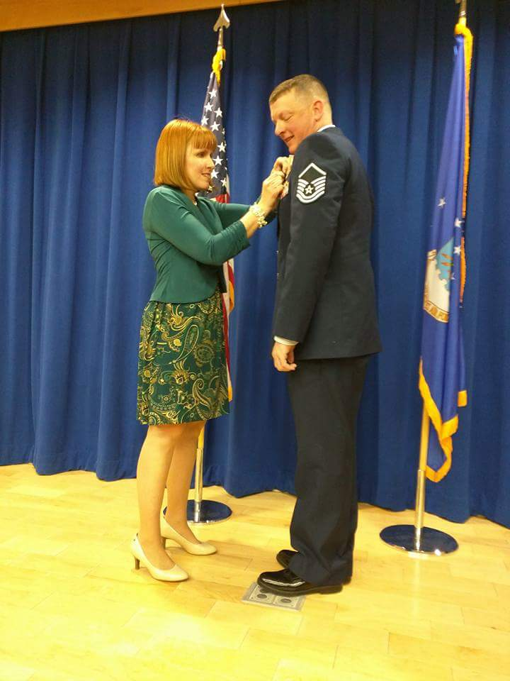 A woman pinning a pin onto a man in an Air Force uniform.